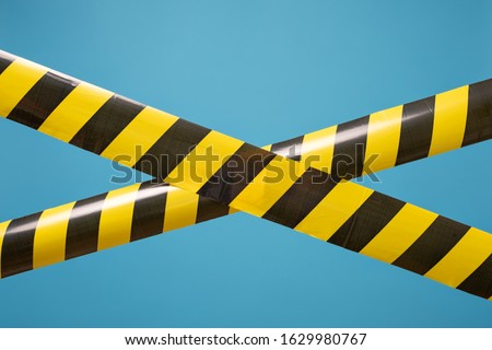 Black and yellow lines of barrier tape forbids passage. Concept of No entry. Protection from coronavirus. Royalty-Free Stock Photo #1629980767