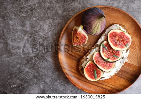 Rye and spelt sourdough toast with creamy yogurt and feta cheese, fresh figs with honey, next to pieces of fresh figs with cinnamon on a large wooden plate. Copy space. #1630015825