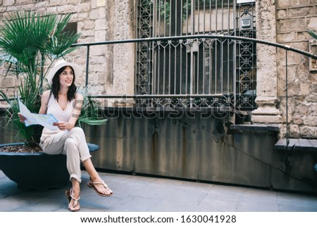 Pensive pleased tourist in casual clothes and hat looking away and making decision while sitting next to small green palms and exploring map against shabby stairs and forged lattice gate in old town #1630041928