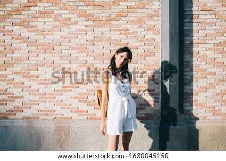 Cheerful playful woman in white short overalls carrying backpack looking at camera standing on street in evening sunlight with brick wall behind #1630045150