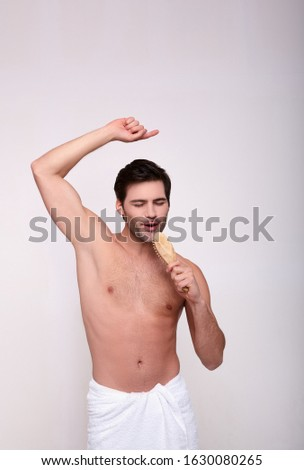 Sexy cheerful athletic white young man after a shower, holds a comb in his hand and closes his eyes, sings. The concept of spa, masculine beauty, masculine morning routine. #1630080265