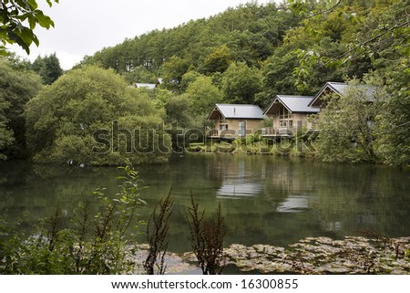 vacation cabins overlooking a lake in the forest #16300855