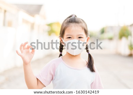 Covid-19 and Air pollution pm2.5 concept.Little chinese girl wearing mask for protect pm2.5 and OK finger hands gesture for stop corona virus outbreak.Wuhan coronavirus and epidemic virus symptoms. #1630142419
