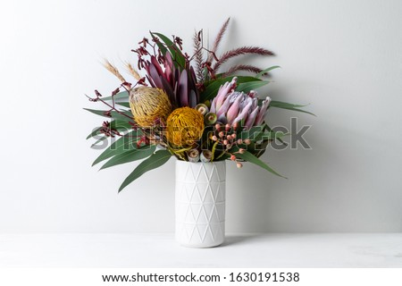 Beautiful floral arrangement of mostly Australian native flowers, including protea, banksia, kangaroo paw, eucalyptus leaves and gum nuts, in a white vase on a white table with a white background. Royalty-Free Stock Photo #1630191538