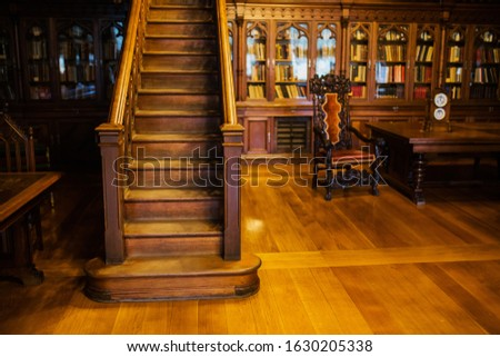 Antique wooden cabinet. Library with bookshelves and desk. Classic interior. Books on the shelves. Wooden stairs. Vintage office #1630205338