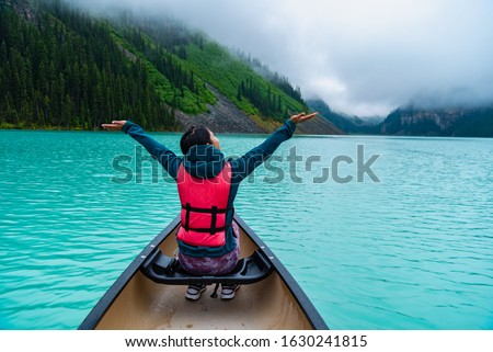 Woman enjoying the view of Lake Louise from Canoe #1630241815