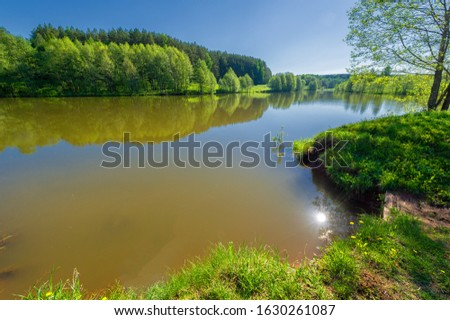 The lake is a large body of water surrounded by land. Walnut and pine trees grow along the edge, complete calm, beautiful hatching in the water #1630261087