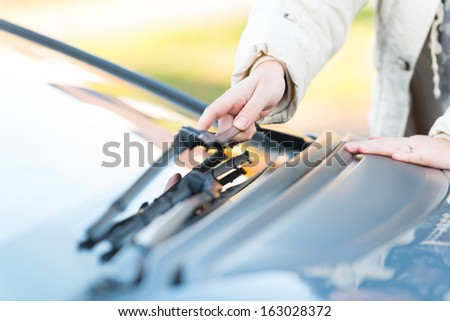 Woman's hand picking up windscreen wiper Royalty-Free Stock Photo #163028372
