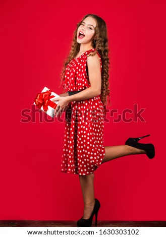 Fashion clothes. Womens day. Surprise for pinup girl. Retro party. Retro girl present wrapped box. Happy valentines day. Birthday gift box. Shopping sales. Adorable child consumer red background. #1630303102