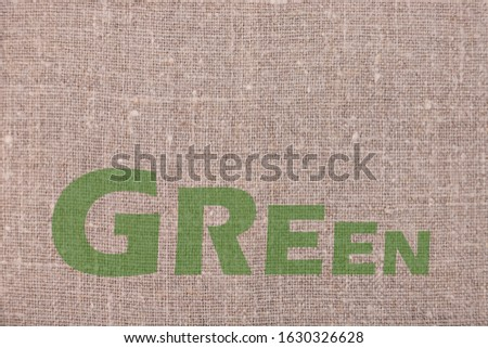 The inscription GREEN on linen natural background. Ecology protection concept. #1630326628
