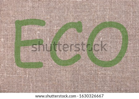 The inscription ECO on linen natural background. Ecology protection concept. #1630326667