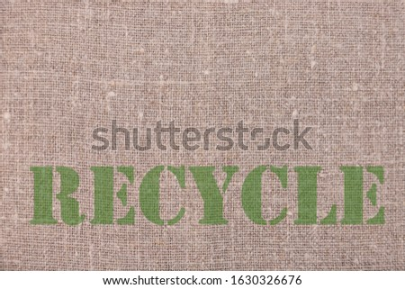 The inscription RECYCLE on linen natural background. Ecology protection concept. #1630326676