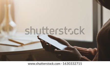 Silhouette of beautiful woman holding and using her blank screen smartphone at the modern circle desk. Relaxing after finished work concept. Royalty-Free Stock Photo #1630332715