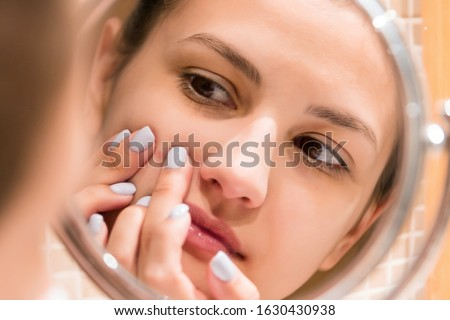 Young girl squeezes pimple on the fer face in front of a bathroom mirror. Beauty skincare and wellness morning concept. #1630430938