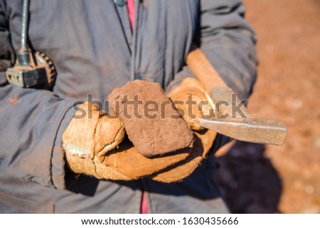 Bauxite ore specimen sample raw mineral with hammer in miner geologyst hands #1630435666
