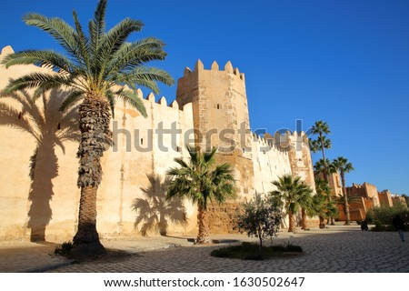 The impressive ramparts of the medina surrounded by colorful palmtrees and a large cobbled walkway in Sfax, Tunisia #1630502647