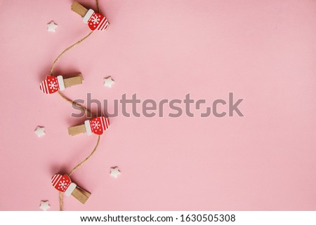 Christmas decorations decorative background. Decorative pins in the form of red gloves on a pink background. Top view, minimalism, flat lay. #1630505308