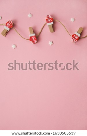 Christmas decorations decorative background. Decorative pins in the form of red gloves on a pink background. Top view, minimalism, flat lay. #1630505539