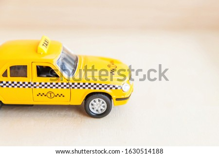 Simply design yellow vintage retro toy car Taxi Cab model on wooden background. Automobile and transportation symbol. City traffic delivery urban service idea concept. Copy space #1630514188