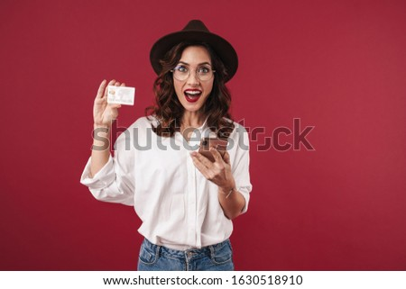 Picture of surprised optimistic young woman in glasses isolated over red wall background using mobile phone holding credit card.