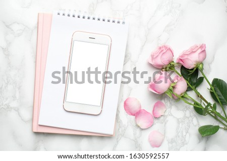Mobile phone with pink roses flowers on marble background.Minimalistic composition for the holidays,valentines day and womens day.