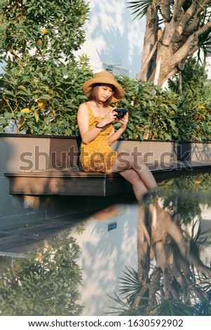 smiling young Asian woman using a camera to take photo outdoors at the park