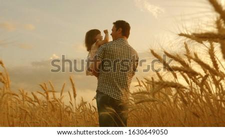 farmer carries little daughter in his arms through a field of wheat. happy child and father are playing in field of ripening wheat. baby boy and dad travel on field. kid and parent play in nature. #1630649050