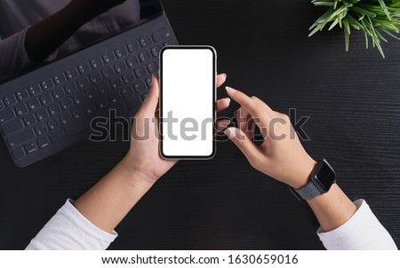 a woman holding phone showing white screen on top view