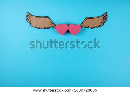 Two hearts with cartoon wings on the blue background. St. Valentine's day celebration.  Copy space.