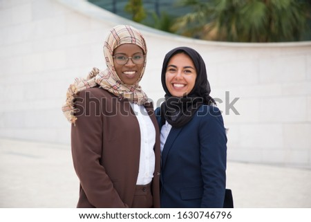 Two confident Muslim women looking at camera. Beautiful cheerful businesswomen posing on street. Female confidence concept #1630746796