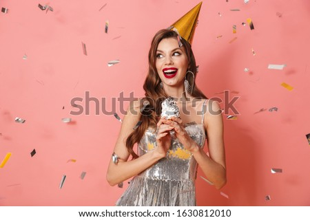 Picture of a young happy woman in bright sequins dress isolated over pink wall background holding cupcake wearing holiday birthday hat over confetti.