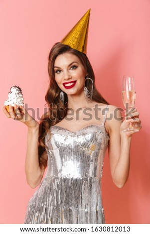 Picture of a young smiling optimistic woman in bright sequins dress isolated over pink wall background holding cupcake and glass with champagne wearing holiday birthday hat.