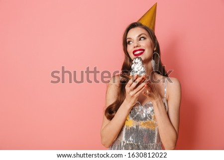 Picture of a young happy woman in bright sequins dress isolated over pink wall background holding cupcake wearing holiday birthday hat.