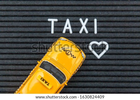 Simply design yellow toy car Taxi Cab model with inscription TAXI letters word on black background. Automobile and transportation symbol. City traffic delivery urban service idea concept. Copy space #1630824409