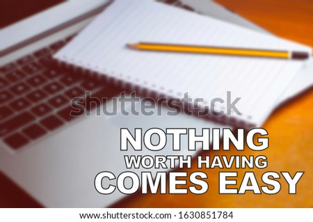 Blurry image of notepad and notebook with motivation quotes - Nothing Worth Having Comes Easy #1630851784