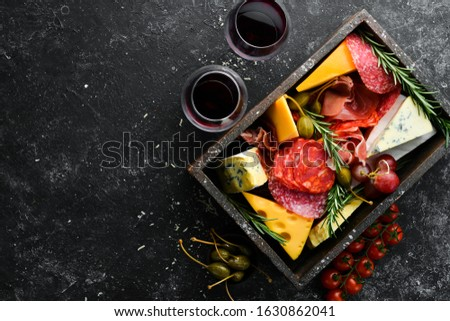 Italian appetizers. Cheese, wine, salami and prosciutto on a black stone background. Top view. Free space for your text. #1630862041