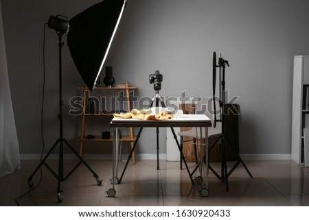 Interior of modern photo studio with professional equipment and drink on table