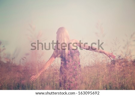 Retro toned portrait of young girl in summer field from back #163095692