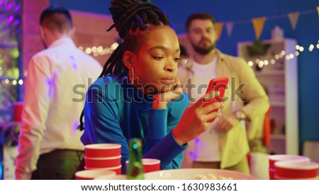 Unsociable afro-american glamorous girl browsing news on smartphone staying online while her friends dancing and having fun. Outsider. Concept of nomophobia. #1630983661