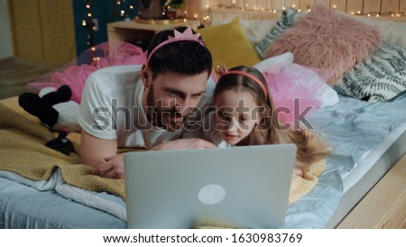 Cheerful father and his girl daughter dressed likfe funny pink fairies lying down on bed watching cartoons together laughing and smiling indoors. Happy birthday party.