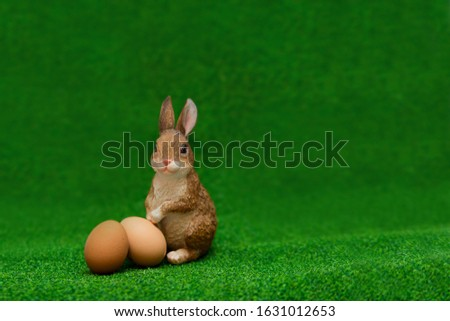 fluffy artificial toy easter bunny with beige eggs sits on the green grass. Copyspace.