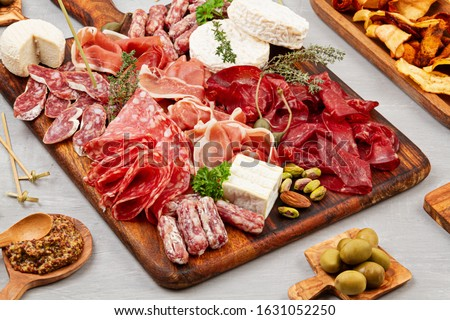 Appetizers table with differents antipasti, charcuterie, snacks and wine. Sausage, ham, tapas, olives, cheese and crackers for buffet party. Top view, flat lay Royalty-Free Stock Photo #1631052250