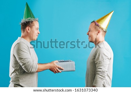 Horizontal studio side view portrait shot of young adult man giving birthday gift to his twin brother