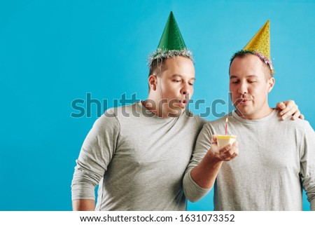 Horizontal studio portrait shot of young adult twin brothers standing together with small piece of birthday cake blowing out candle, blue background