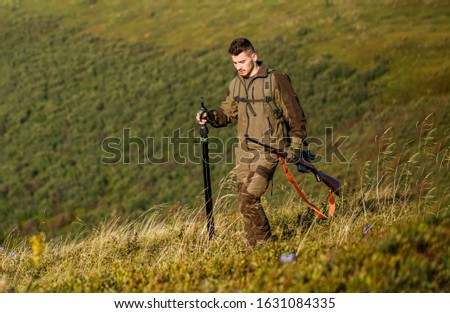 Hunt hunting rifle. Hunter man. Hunting period. Male with a gun. Close up. Hunter with hunting gun and hunting form to hunt. Hunter is aiming. Shooter sighting in the target. The man is on the hunt. #1631084335