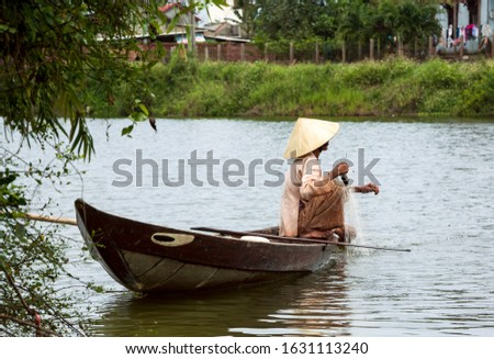 Traditionally dressed, old Vietnamese lady with conical straw hat skilfully net fishing in her small  boat, Hoi An, Vietnam, Indochina, Southeast Asia, Asia. #1631113240
