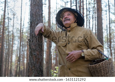 Old man walking standing near tree in forest resting enjoying the moment holding busket an hands. Senior mushroomer in summer forest #1631121292