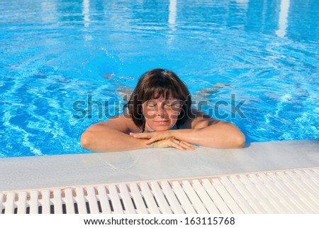 middle-aged brunette on a sun lounger by the pool #163115768