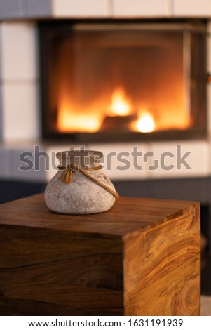 Glass vase with a cord on a wooden box in front of a blurred background with a fireplace, romantic scene