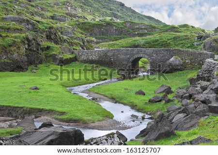 An old stone bridge carries a narrow road across the winding Serpent River in the rocky terrain near the Gap of Dunloe, famous tourist destination near Killarney, County Kerry, Ireland. #163125707